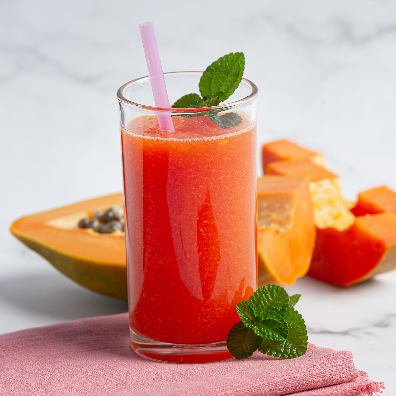 a glass of papaya juice put on white marble floor