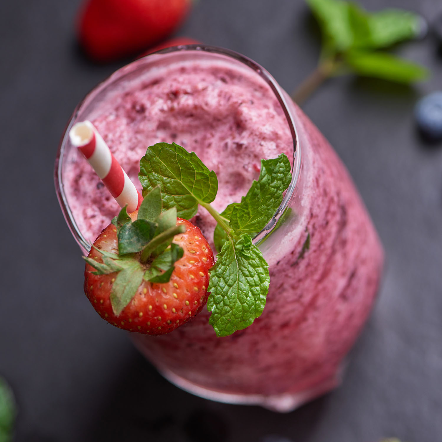 Delicious strawberry, mulberry and blueberry smoothie garnished with fresh berries and mint in glass. soft focus. beautiful appetizer pink raspberries, well being and weight loss concept.